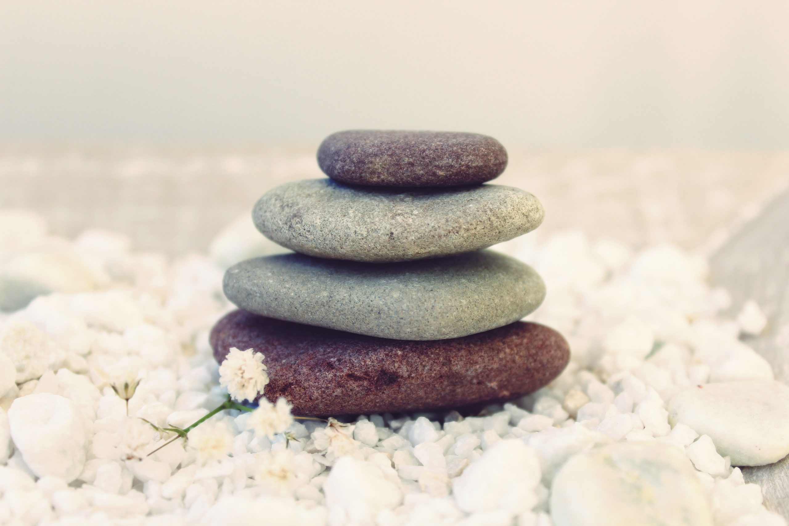 Pile of four coloured pebbles symbolising body, heart, mind, spirit, in a whole person