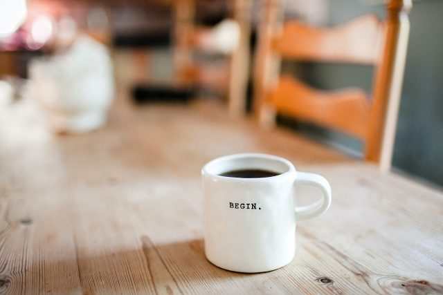 Coffee cup on a table with the word begin written on it